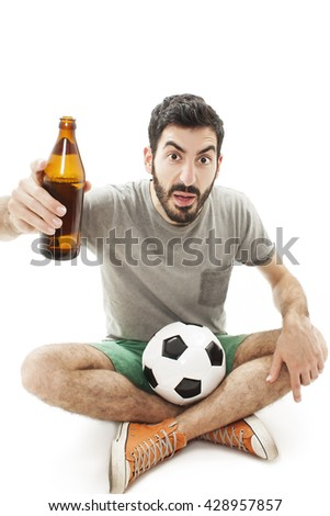 Young shocked emotional supporter sitting on the floor and watching soccer with beer. Isolated on white background - stock photo