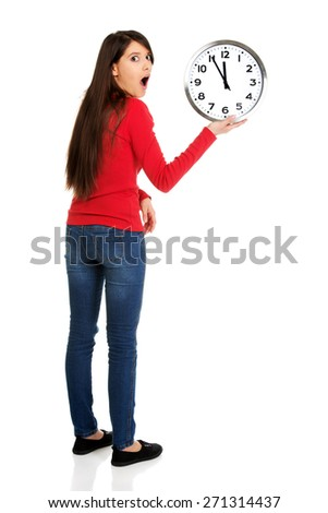 Young shocked student woman with the clock. - stock photo