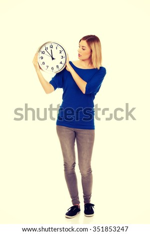 Young shocked woman holding a clock.  - stock photo