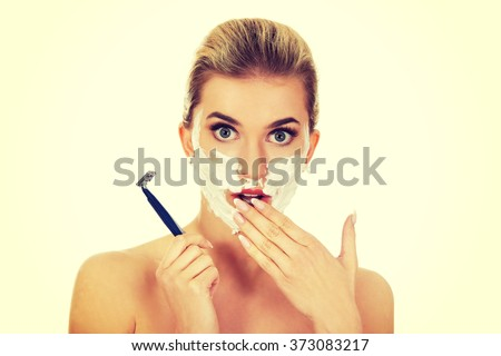 Young shocked woman shaving her face with a razor - stock photo