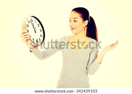 Young shocked woman with a clock. - stock photo