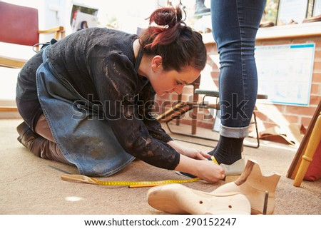 Young shoemaker measuring customers feet - stock photo