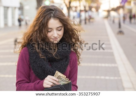 young shopper woman taking out money from wallet on street  - stock photo
