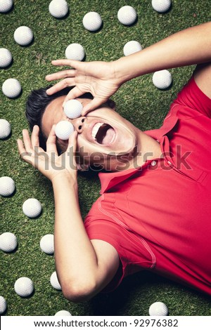Young shouting male golf player in red shirt lying on green next to several golf balls and covering his eyes with two golf balls. - stock photo