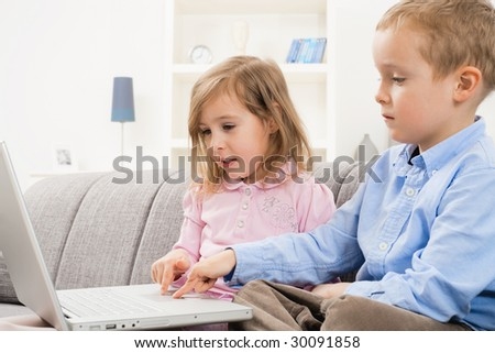 Young siblings sitting on couch at home, browsing internet on laptop computer, looking at screen. - stock photo