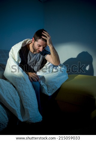young sick man sitting on couch at home scary and desperate suffering insomnia, depression, nightmares, emotional crisis, mental disorder with a dim light and deep dark shadows - stock photo