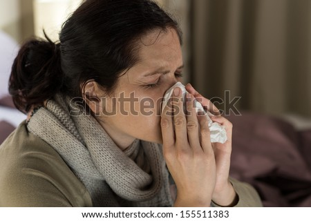 Young sick woman sneezing in tissue sweating from flu fever - stock photo