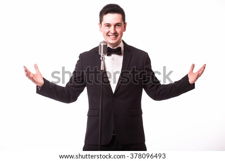 Young singer in suit singing with the microphone with open hands. Isolated on white background. Singer concept. - stock photo