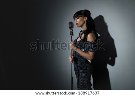 Young Singer with microphone over back background - stock photo