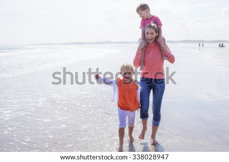 Young single mother at the beach with her son and daughter. They are laughing and are barefoot in the water. - stock photo
