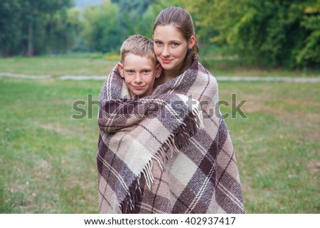Young sister and brother with freckles on their faces stand covered with plaid in park, get warm, smiling and looking at camera. - stock photo