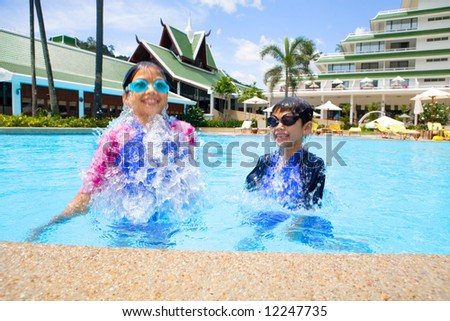 Young sister and her brother jumping up from beneath the water, laughing and enjoying themselves. - stock photo