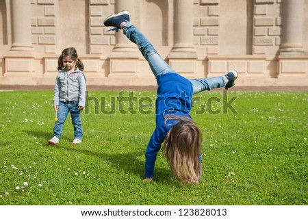Young sisters playing outdoors. - stock photo