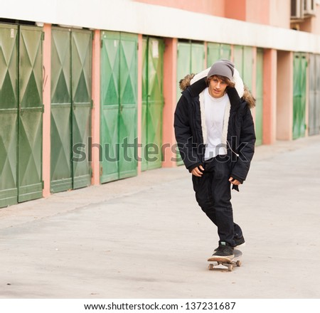 young skater rolling down the street - stock photo
