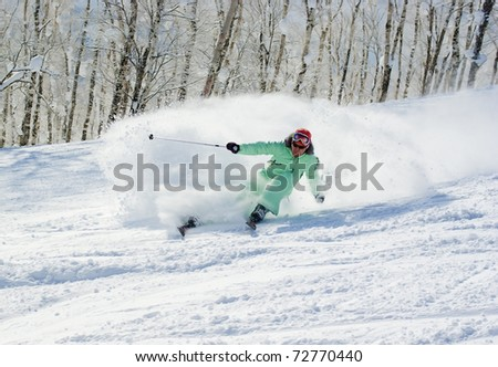 Young ski racer rushing downhill - stock photo