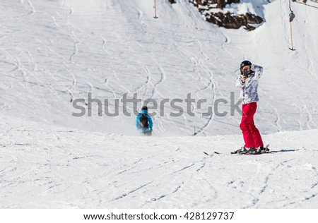Young skier woman taking a photo with mobile phone - stock photo