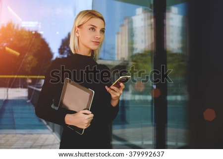 Young skilled businesswoman hold touch pad and cell telephone while waiting for a meet with partner, female assistant with mobile phone wait for her boss while standing outside modern office building - stock photo