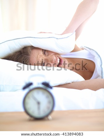 Young sleeping woman and alarm clock in bedroom at home - stock photo