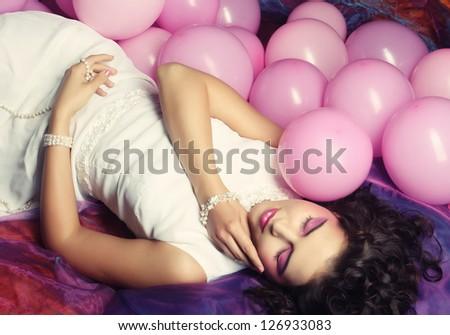 young sleeping woman lying on floor among balloons - stock photo