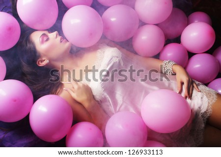 young sleeping woman lying on floor among balloons - stock photo