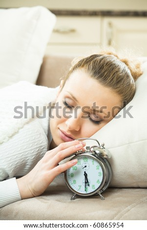 Young sleeping woman with alarmclock at home - stock photo