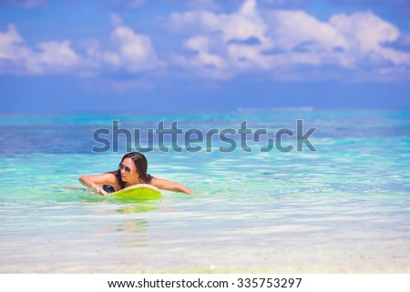 Young slender surf girl at white beach with yellow surfboard - stock photo