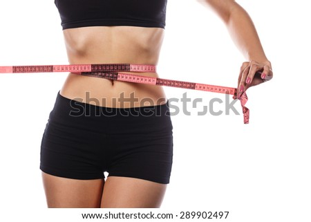 Young slender woman measuring her waist after dieting and exercise sports. Isolated on white background. The concept of excess weight loss and healthy eating. - stock photo