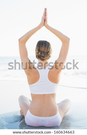 Young slender woman sitting on beach hands raised in prayer sitting on beach - stock photo