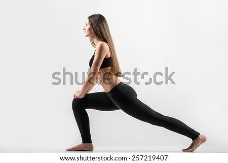 Young slim attractive girl doing lunge exercise, fitness exercises for hips and buttocks - stock photo