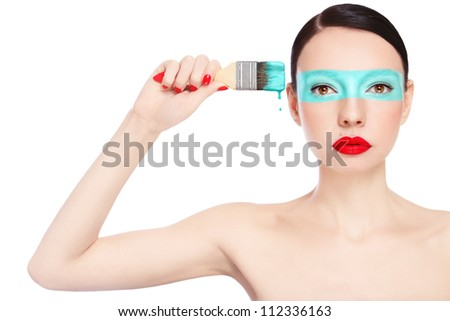 Young slim beautiful woman with painting brush and paint on her face, over white background - stock photo