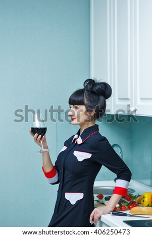 Young slim girl is drinking an aperitif in the kitchen. The girl is preparing dinner. Household chores . - stock photo