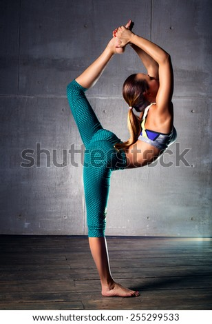 Young slim gymnast woman in sports clothing stretching legs on wall background. - stock photo