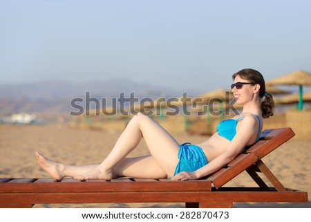 Young slim happy smiling woman in sunglasses lying on sun lounger at exotic beach with golden sand, tanning in sunlight on tropical sea resort - stock photo
