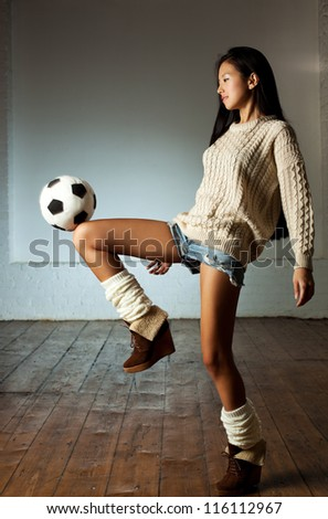 Young slim japanese woman playing toy football. - stock photo