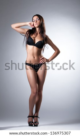 Young slim model posing in black lingerie - stock photo