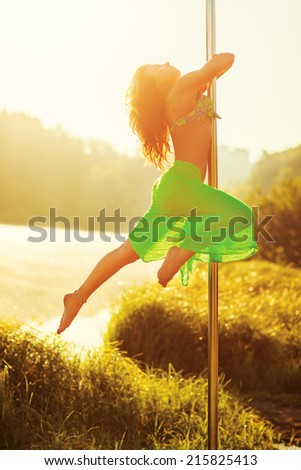 Young slim pole dance woman on lake background. - stock photo
