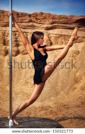 Young slim pole dance woman on sand background. - stock photo