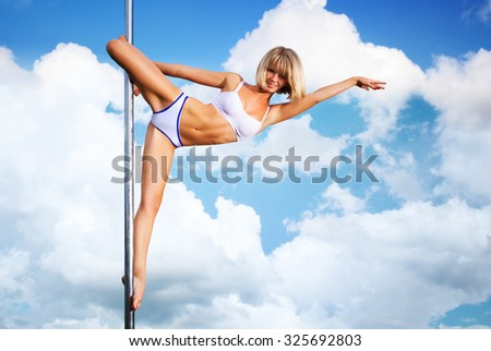 Young slim pole dance woman on sky background. - stock photo