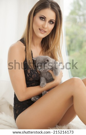 Young slim sexy and attractive brunette woman in black lingerie  on the white fur holding a gray cat - stock photo
