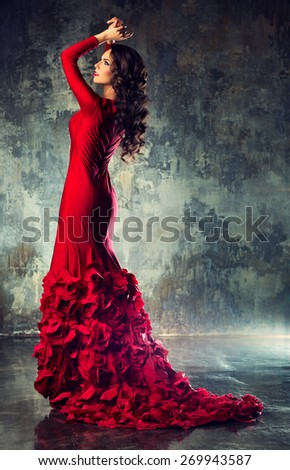 Young slim sexy fashion woman in long red dress standing on stone wall background - stock photo