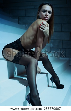 Young slim sexy woman in black lingerie sitting on stairs. Soft night blue tint. - stock photo