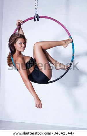 Young slim sports woman in black clothing sitting on ring - stock photo