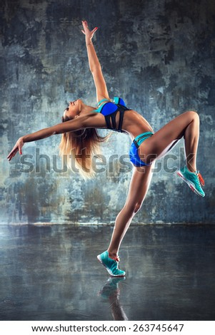 Young slim sports woman stretching and dancing on wall background. - stock photo