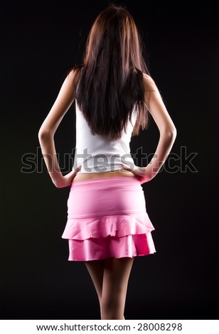 Young slim woman backside view. On dark background. - stock photo
