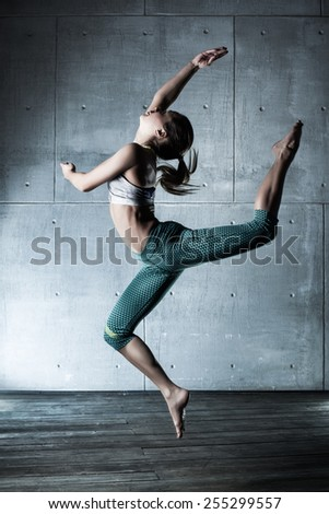 Young slim woman dancer in sports clothing jumping high on wall background. - stock photo