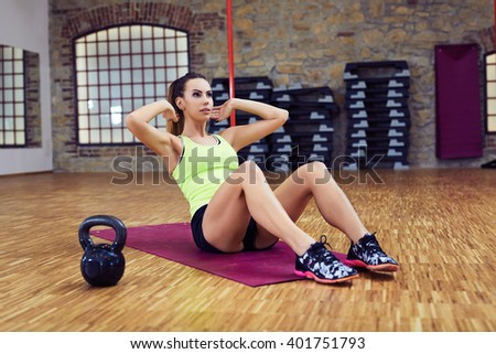 Young slim woman doing sit ups exercise at gym - stock photo
