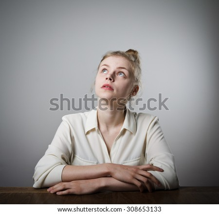 Young slim woman full of doubts and hesitation. Girl solving a problem. - stock photo