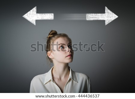 Young slim woman has to decide between two directions. Girl in white full of doubts and hesitation. - stock photo