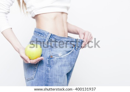 Young slim woman holding an apple and wearing oversize jeans on white  - stock photo