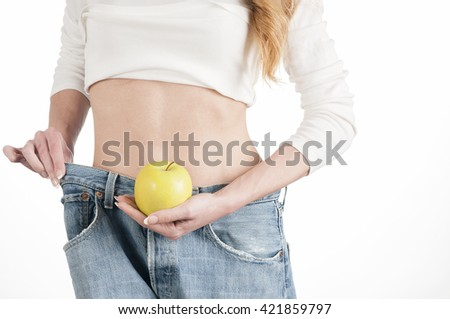 Young slim woman holding an applea and wearing oversize jeans on white  - stock photo